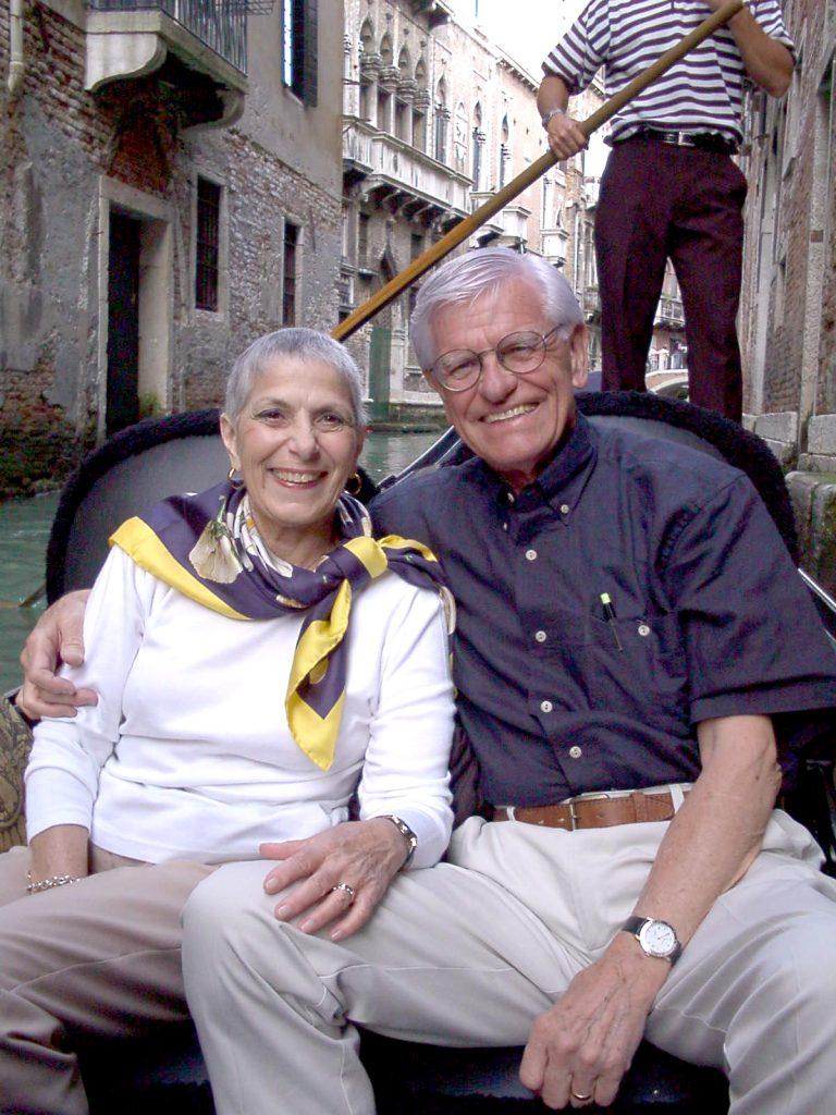 happy senior couple on gondola in Venice