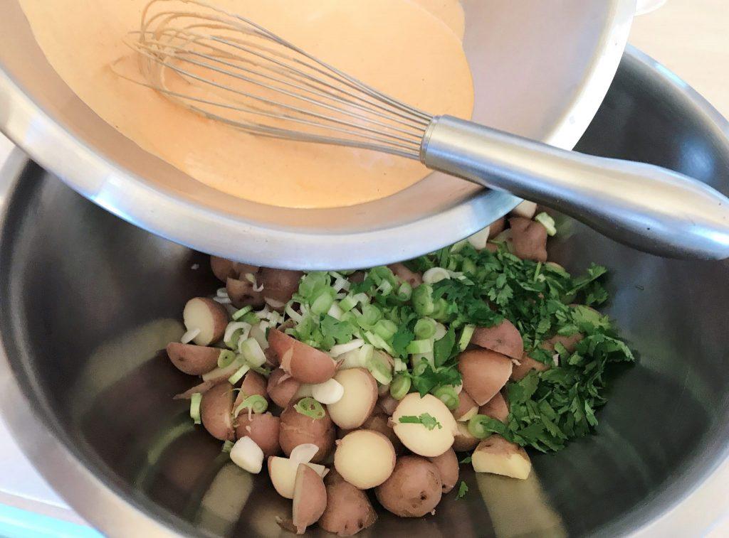 Mixing Tandoori potato salad ingredients