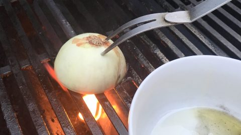 priming the barbecue grill with onion