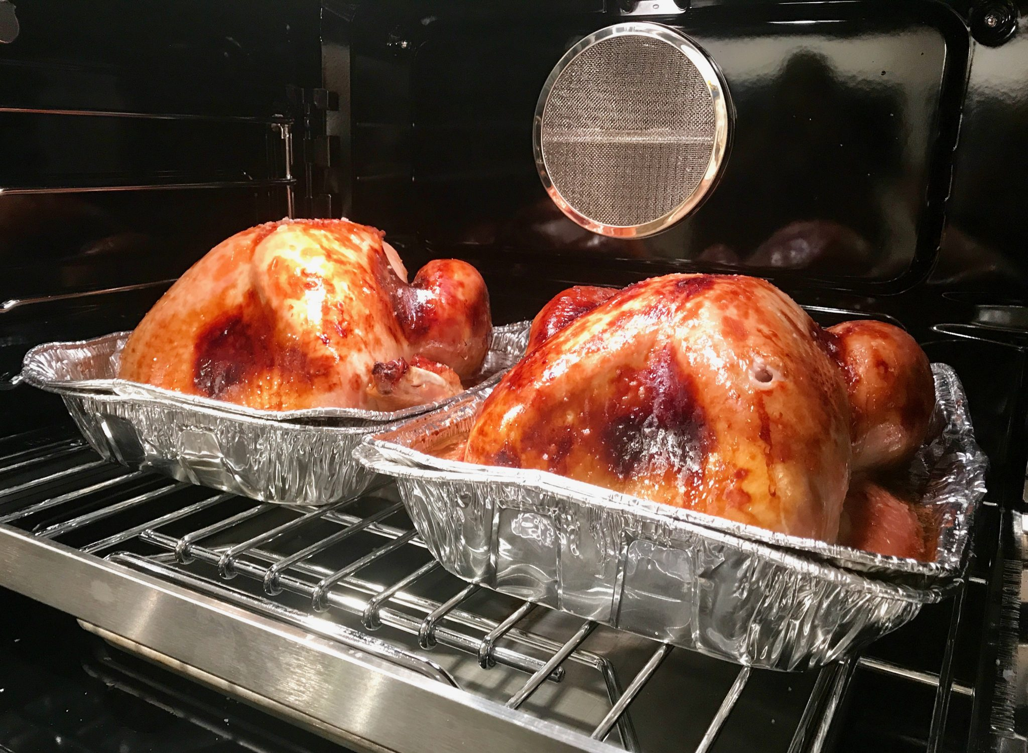 two Thanksgiving turkeys baking in the oven