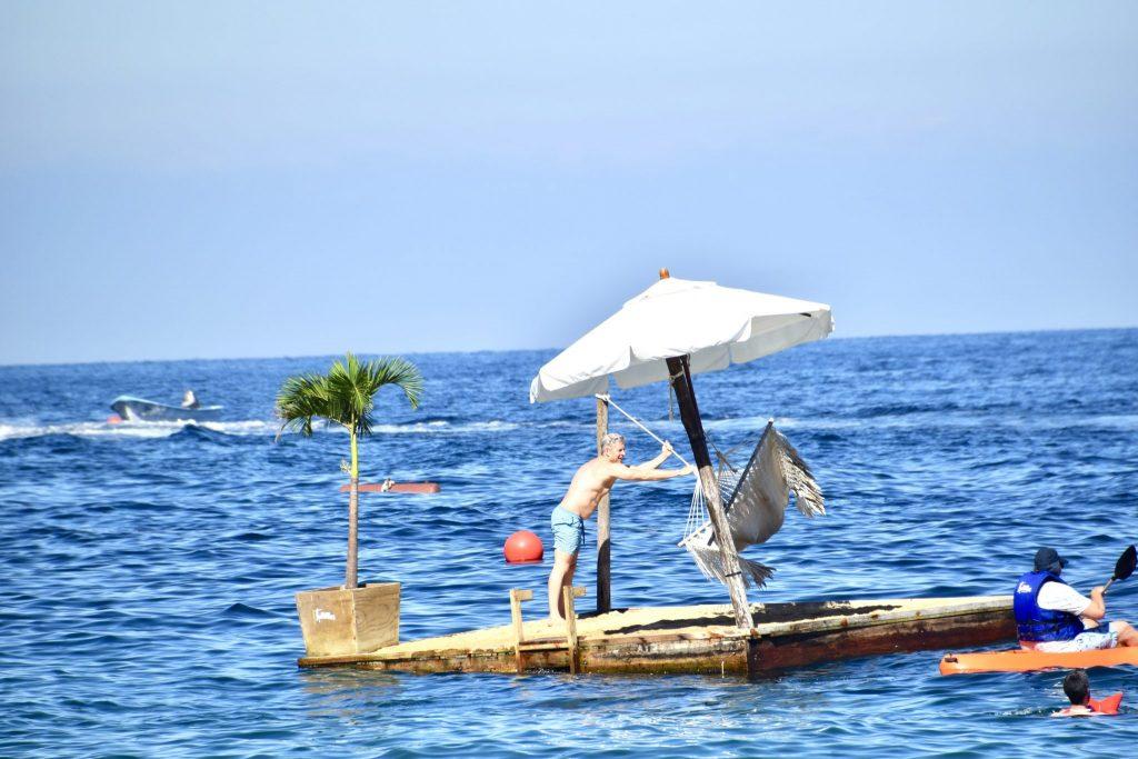 man swinging hammock on floating platform Las Caletas Puerto Vallarta
