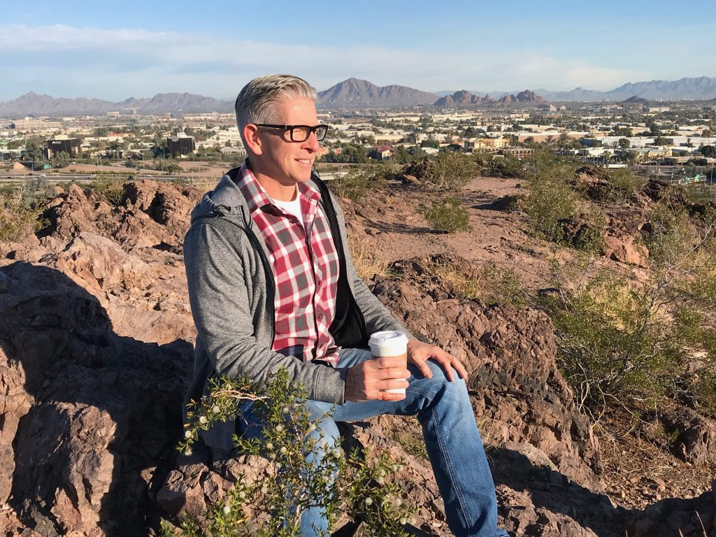 man with views of Phoenix from top of The Buttes Tempe Arizona
