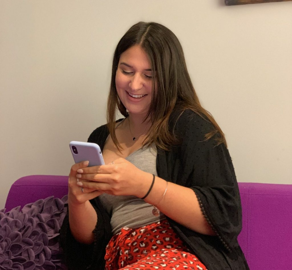 woman on couch smiling at phone