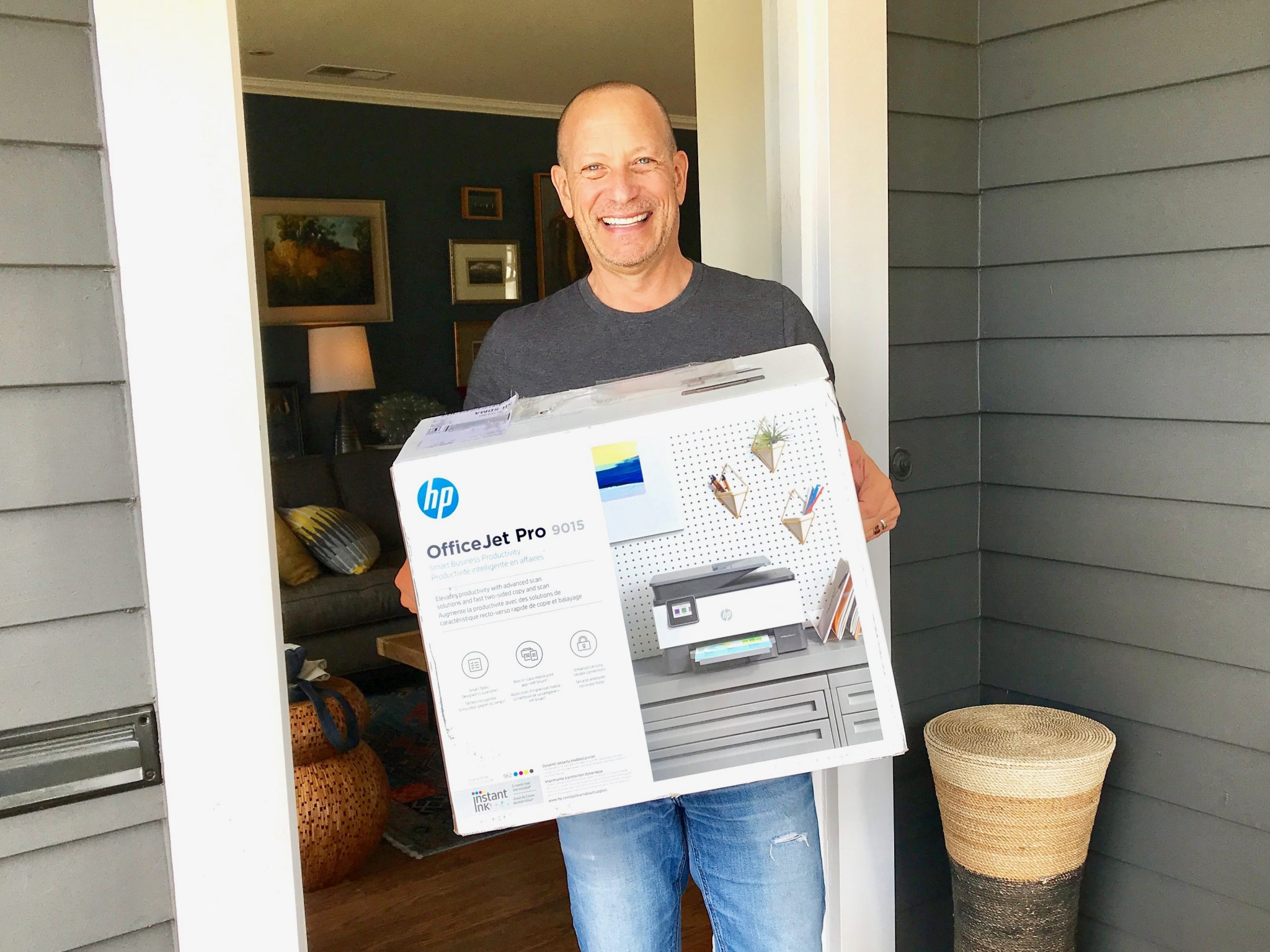 man with HP printer box on front porch