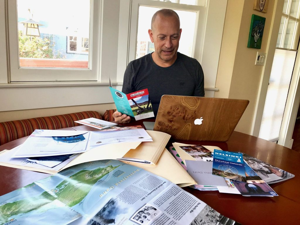 man with brochures and laptop at table