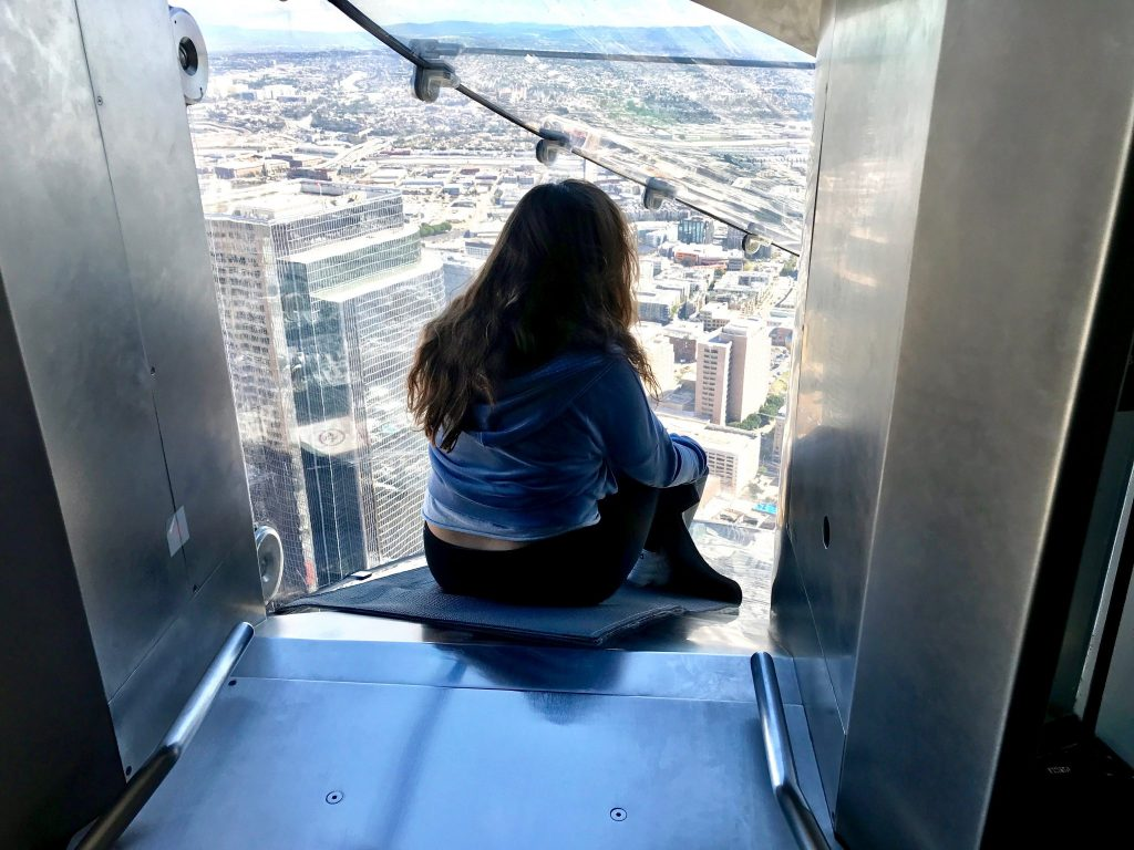 girls slides down OUE Skyspace glass slide