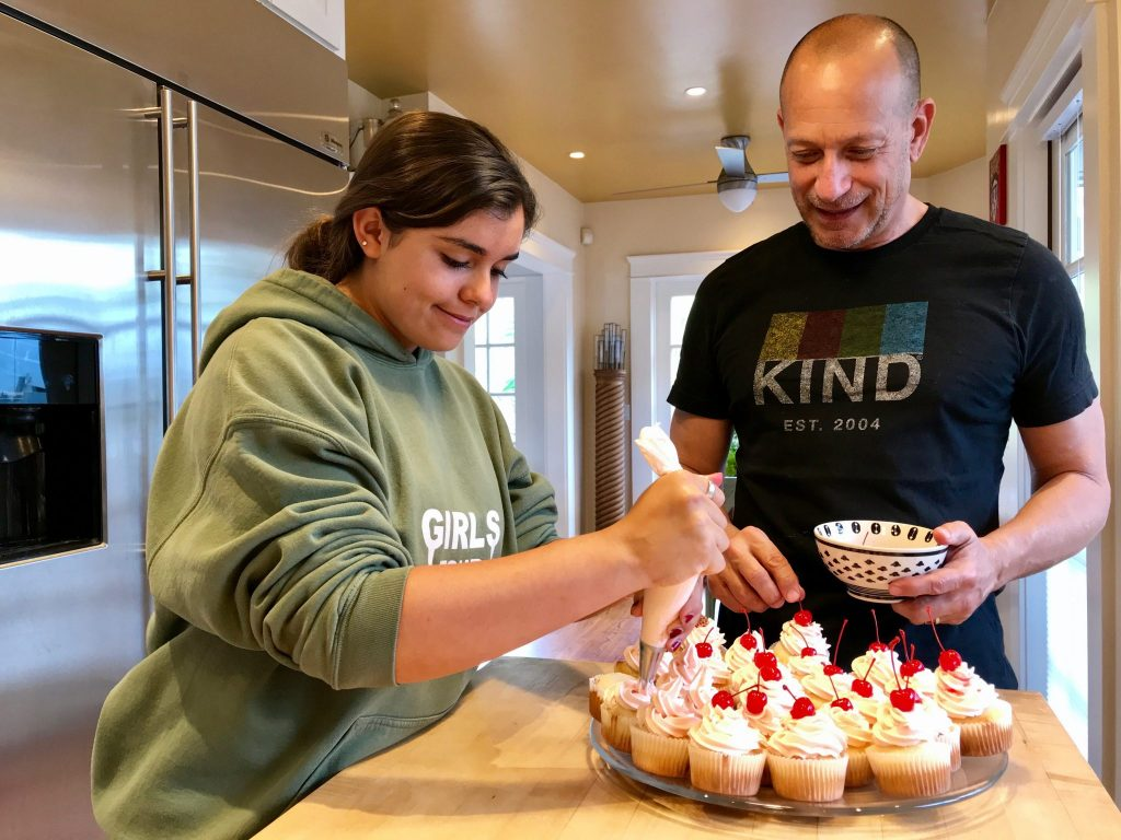 dad and daughter decorating cupcakes