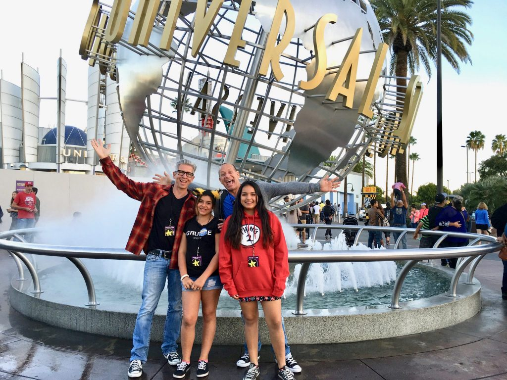 family with Universal Studios Hollywood globe at entrance
