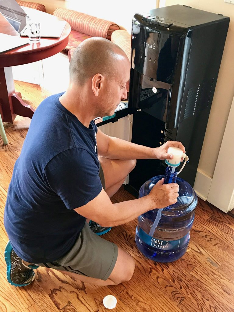 man installing bottom load water bottle in Primo Water Dispenser
