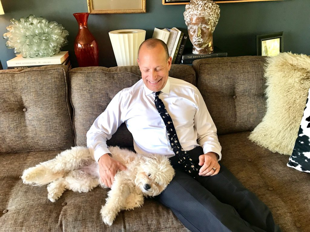 man in tie on couch with dog
