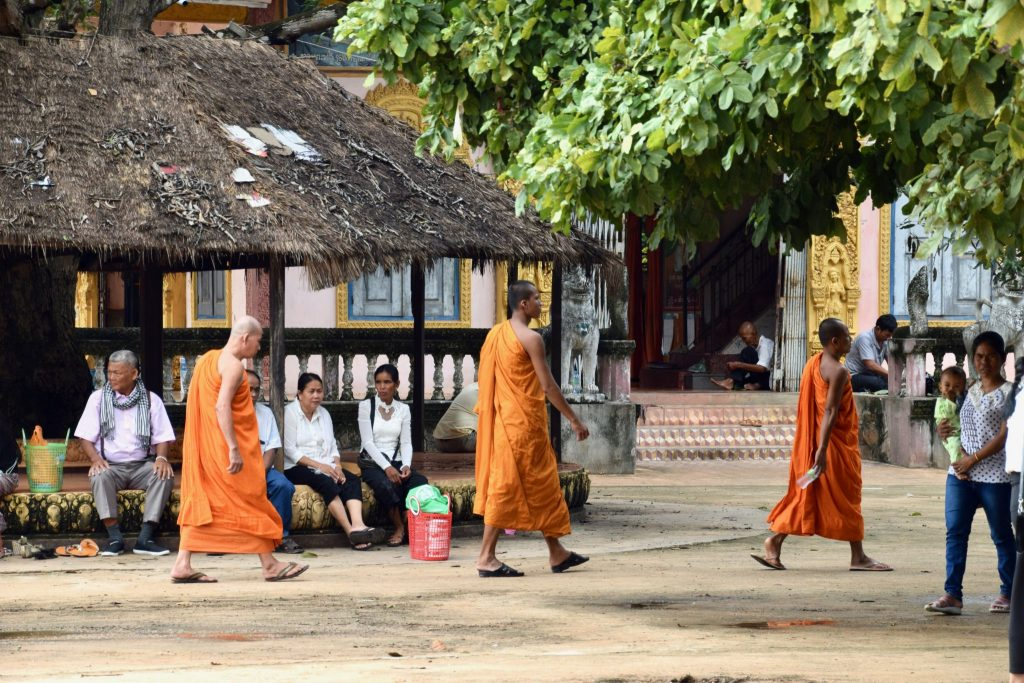 monks walking across plaza at Buddhist monastery in Cambodia