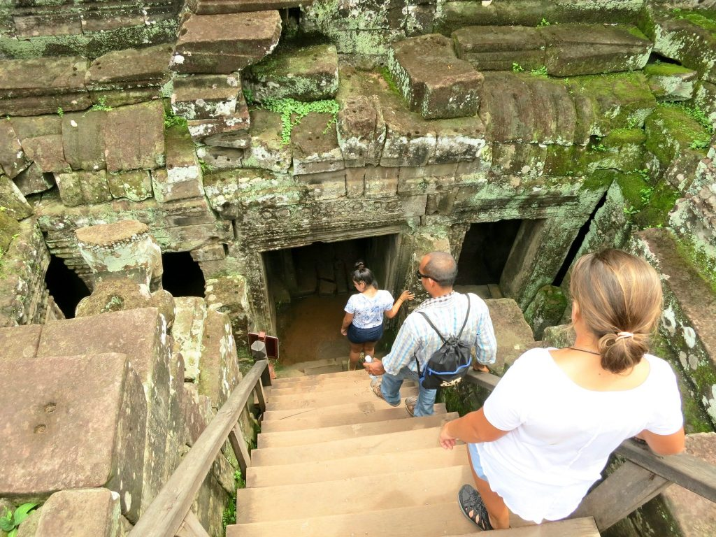 family descends into Temple ruins in Cambodia