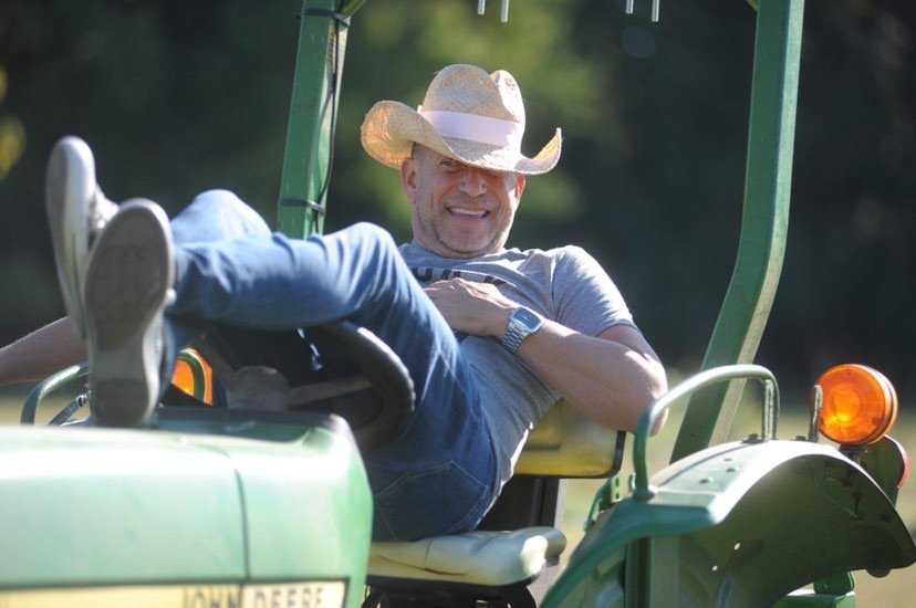 man in cowboy hat lays back in seat of John Deere tractor, Salisbury, Maryland