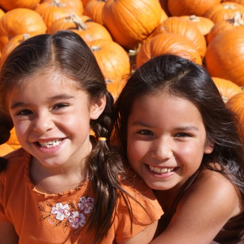 2 girls sitting in a pile of pumpkins