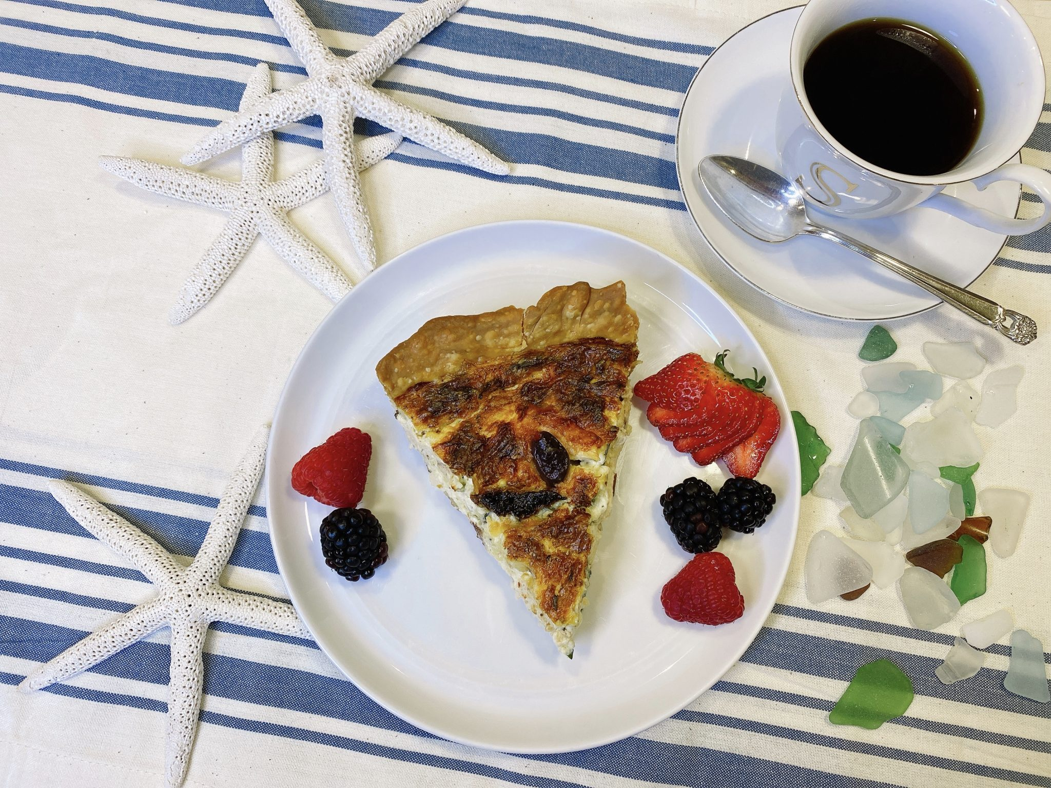 slice of breakfast quiche with berries and coffee