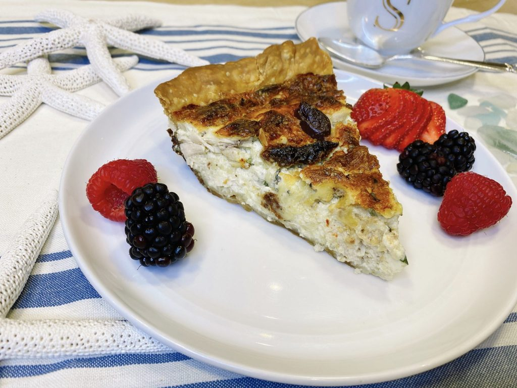 slice of chicken quiche on plate with berries