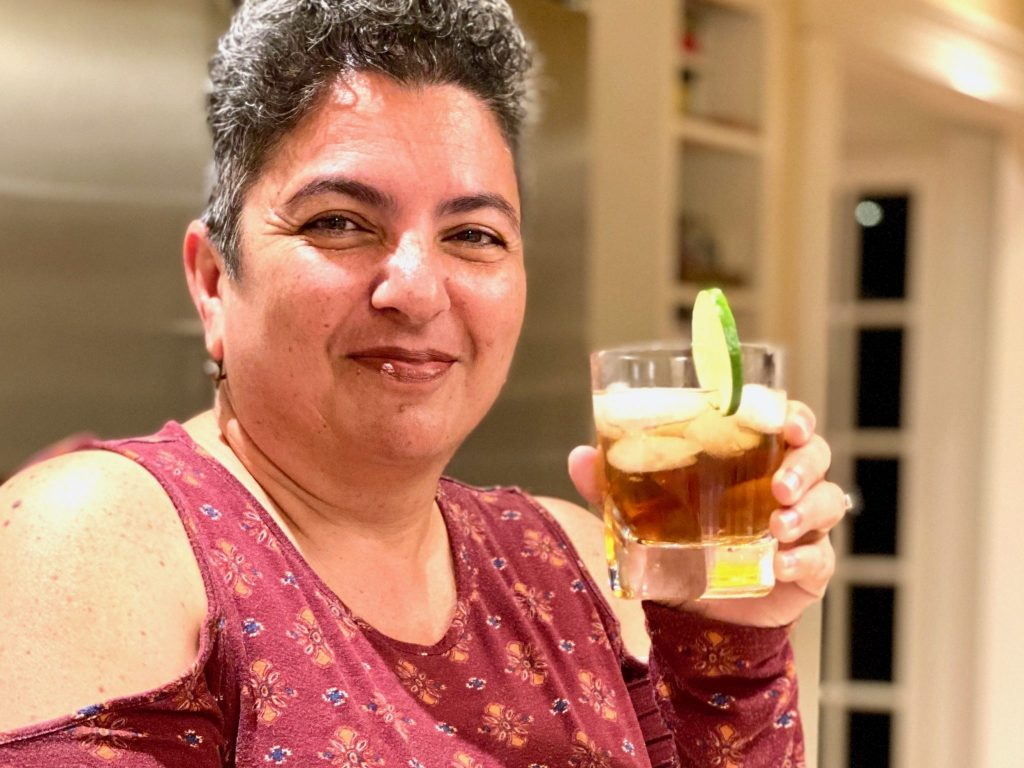 woman enjoys cocktail at house party