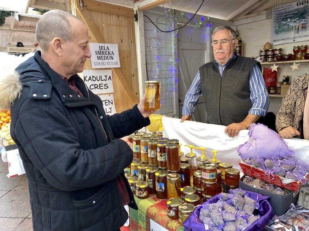 Man shopping Advent Market stalls studies honey jars in Rijeka, Croatia
