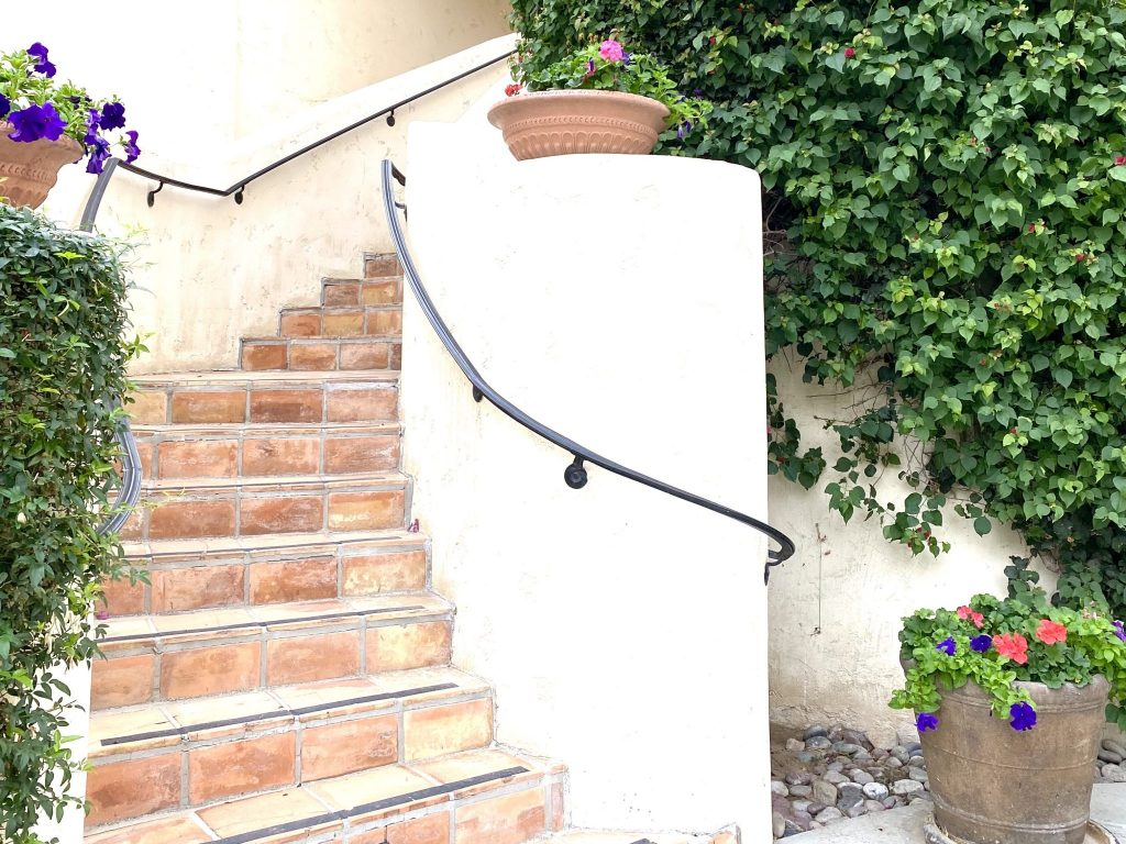 curving staircase and Spanish architecture with pots of flowers