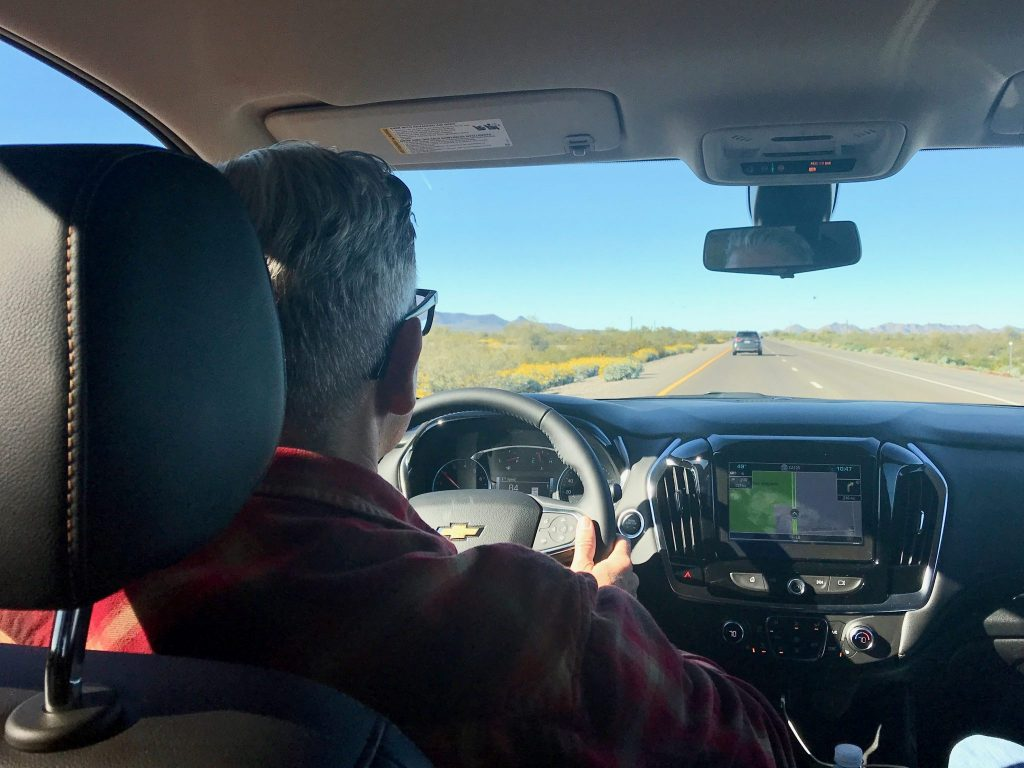 View from backseat of car as driver moves down Arizona highway
