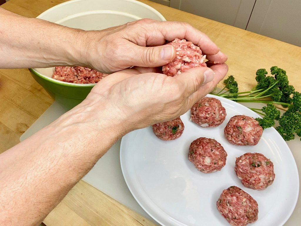 man rolling meatballs to prepare for cooking