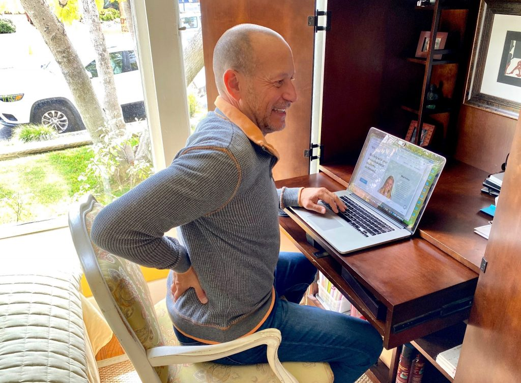 man has back pain while sitting at home work station with laptop