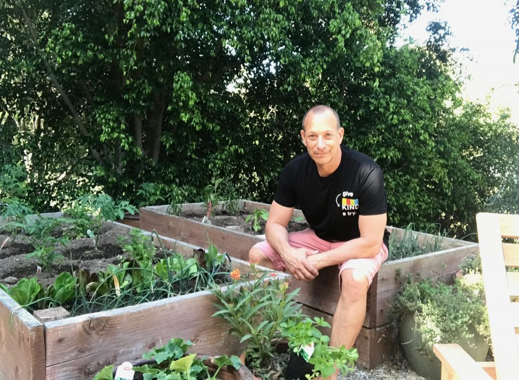 man sitting in his backyard vegetable garden with raised redwood containers filled with vegetable plants