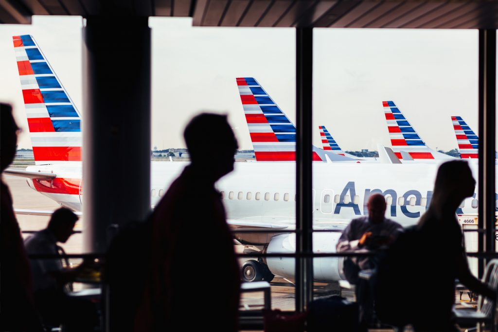 Chicago, IL, USA - July 17, 2017: American Airlines fleet of airplanes with passengers at O'Hare Airport passing through corridor.