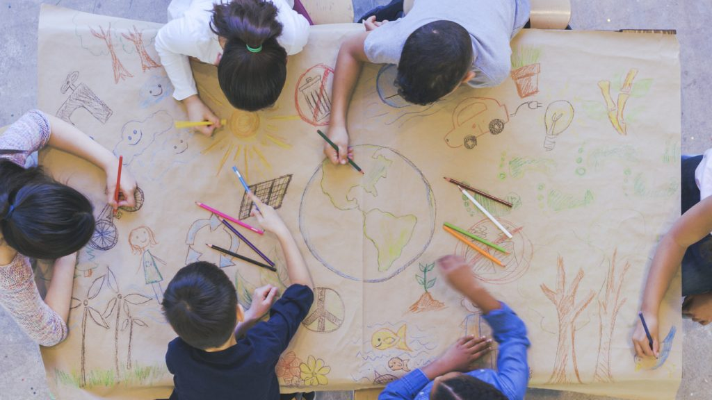 Aerial overhead view of a multi-ethnic group of elementary age children drawing. They are seated around a table. The kids are using colored pencils to make a mural. The have colored a world map, objects found in nature, and symbols of environmental conservation.