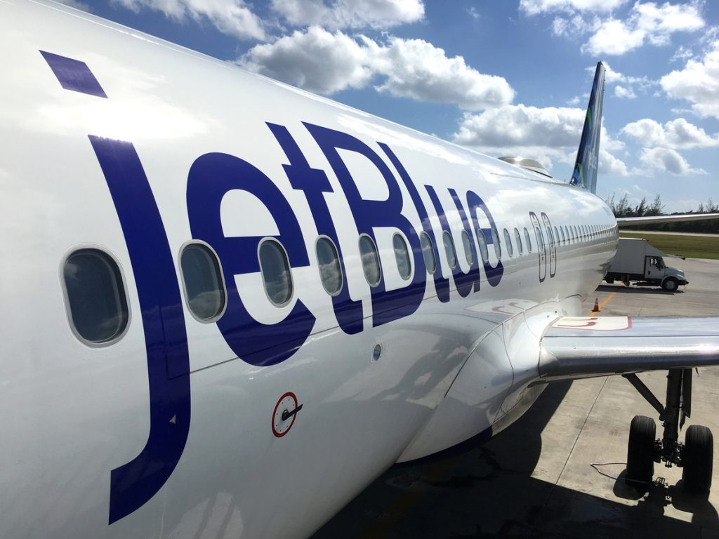 George Town, Cayman Islands - December 21, 2017: Land operations and boarding in Owen Roberts Intl. Airport in Grand Cayman Islands. Close up of a JetBlue plane in a sunny day.