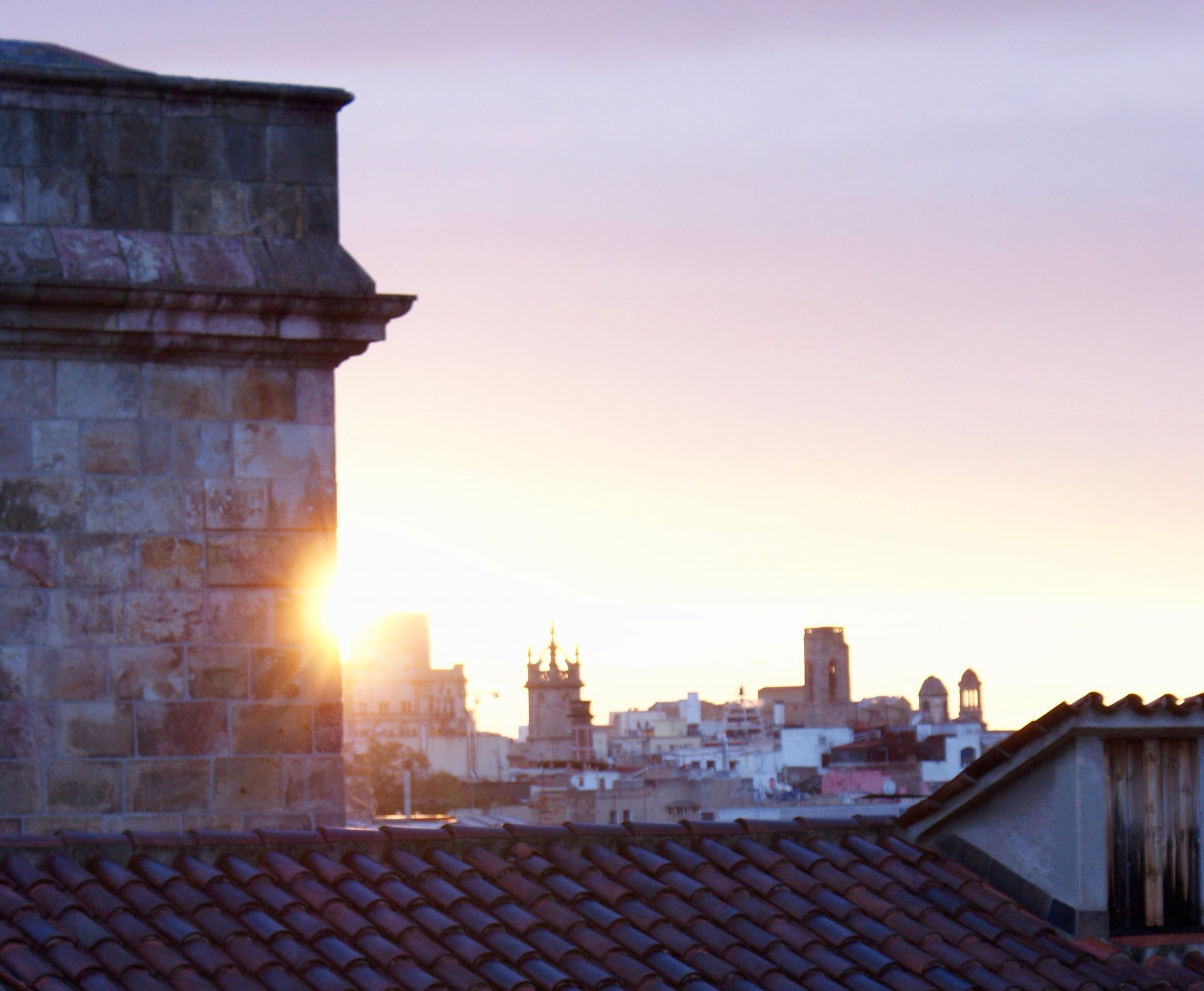looking out at sunrise over rooftops in downtown Barcelona near La Rambla
