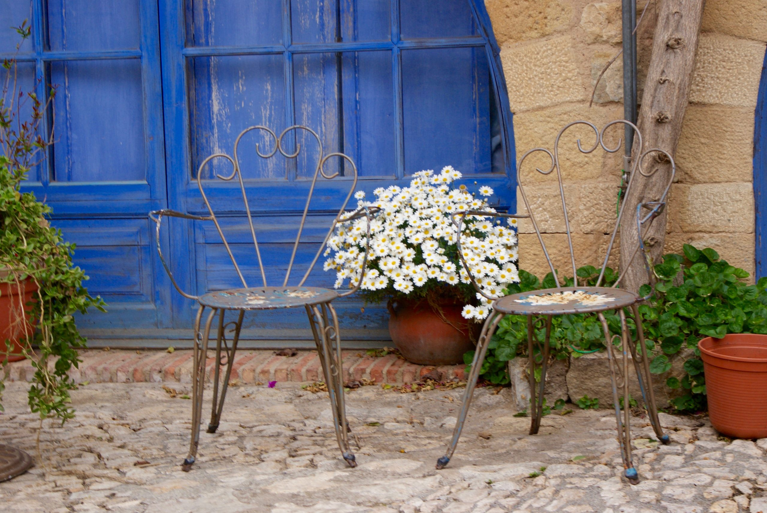 street setting in Spain with two chairs, flowers pots on cobblestone street