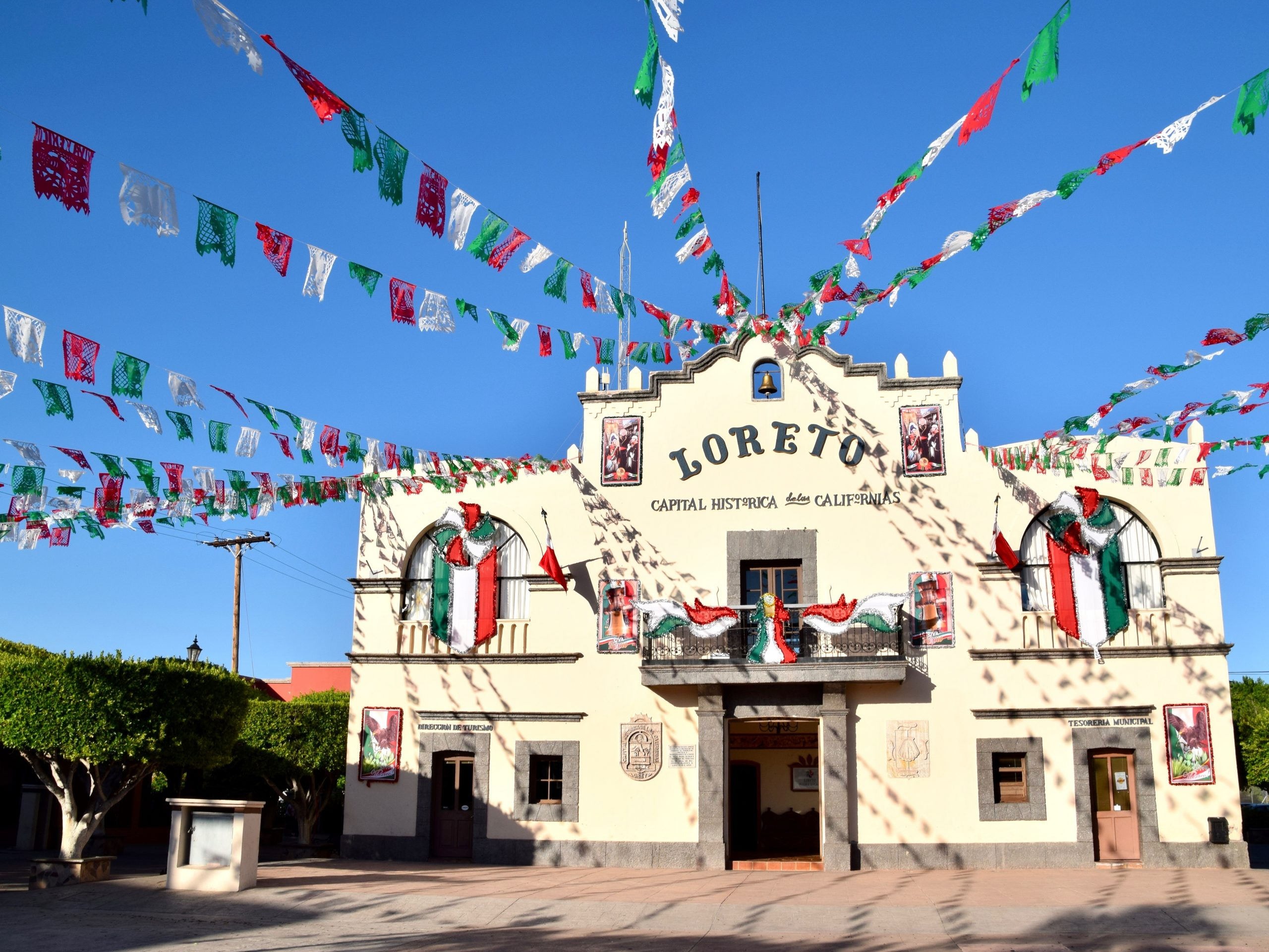 The town square and town hall building with colorful flags and bunting in Loreto, Baja California Sur, Mexico