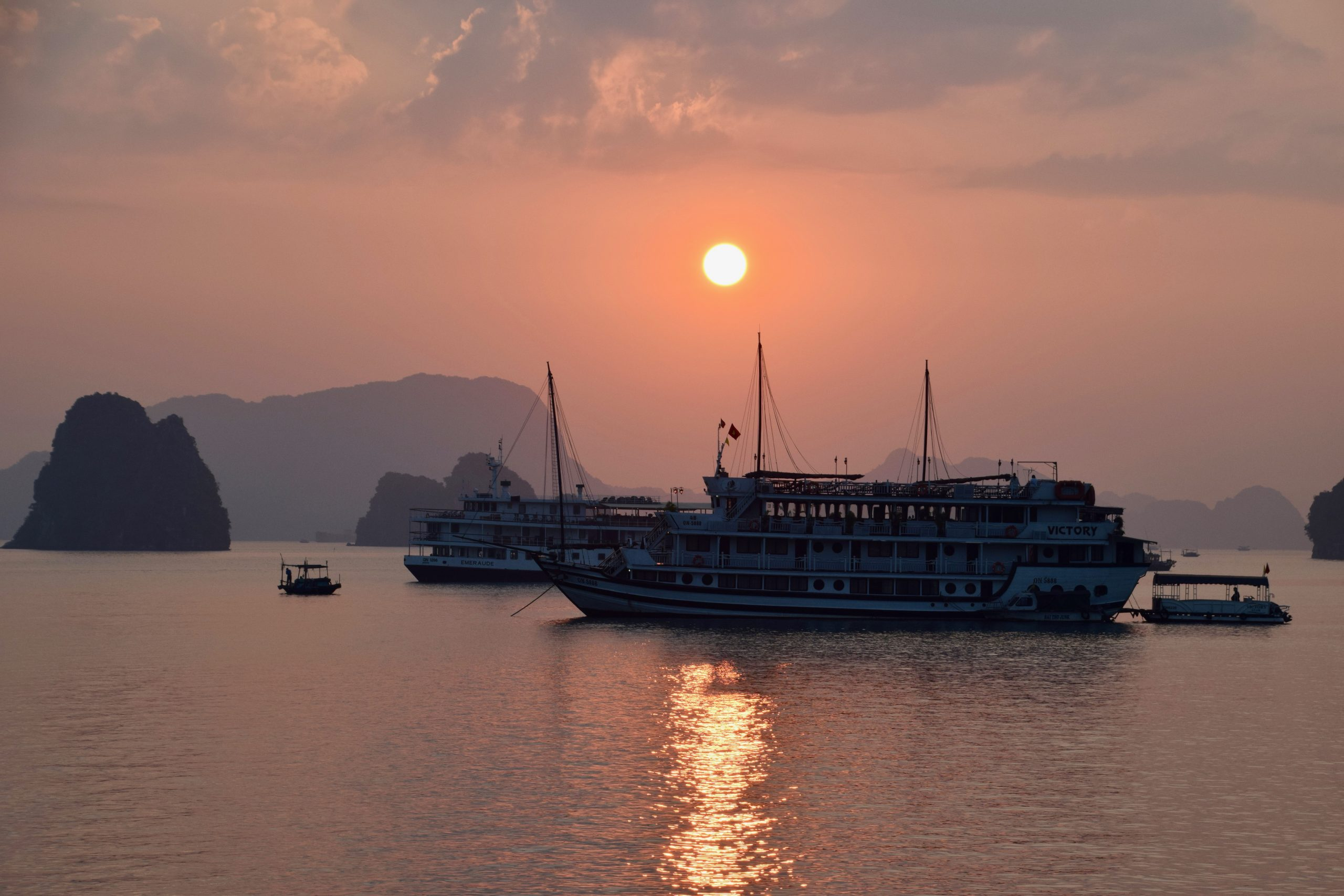 Halong Bay, Vietnam at sunset with the famous islands and junk boats