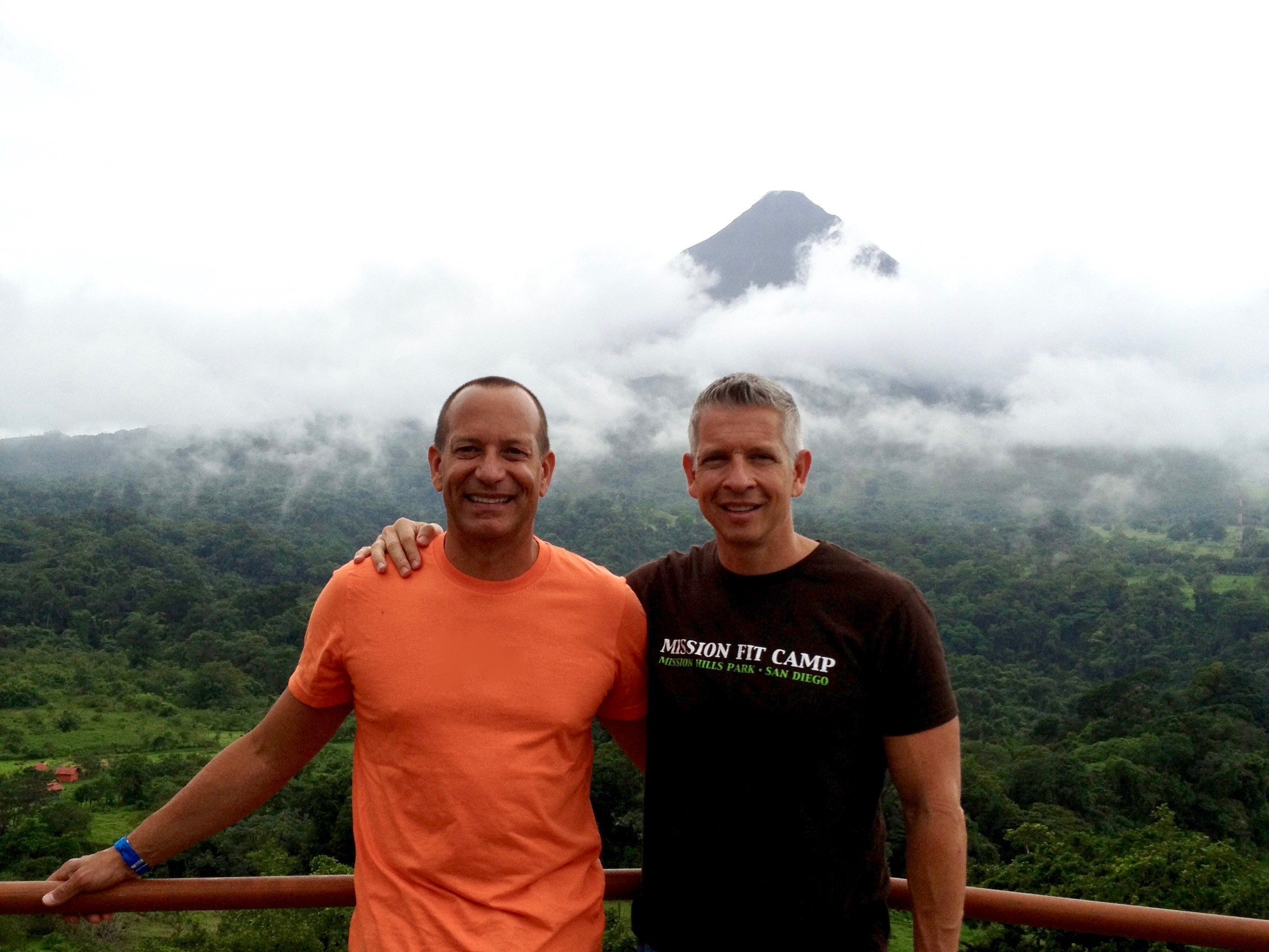 two men standing on an overlook in Arenal, Costa Rice with the volcano in the background