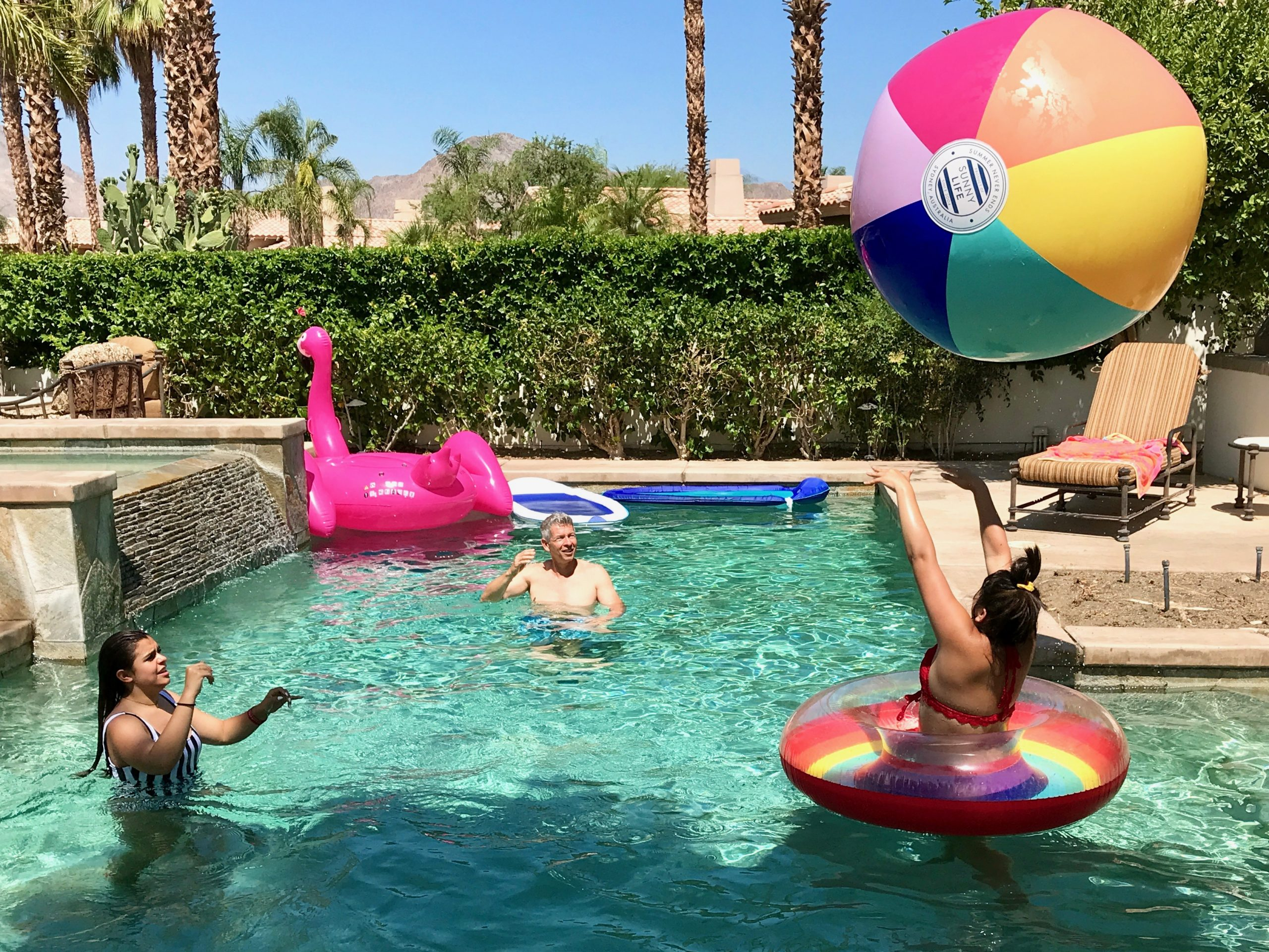 family plays with giant beach ball in Palm Springs pool