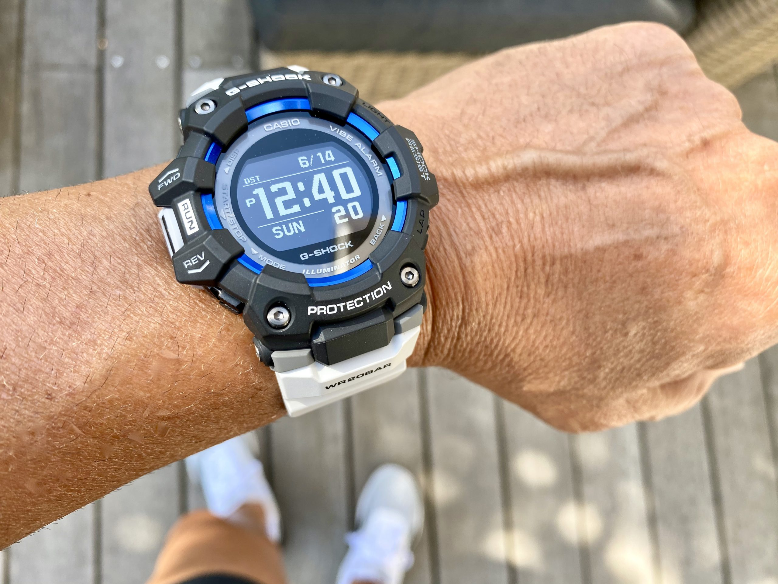 Man's wrist wearing G-SHOCK GBD100 Watch from Casio with black face and white band