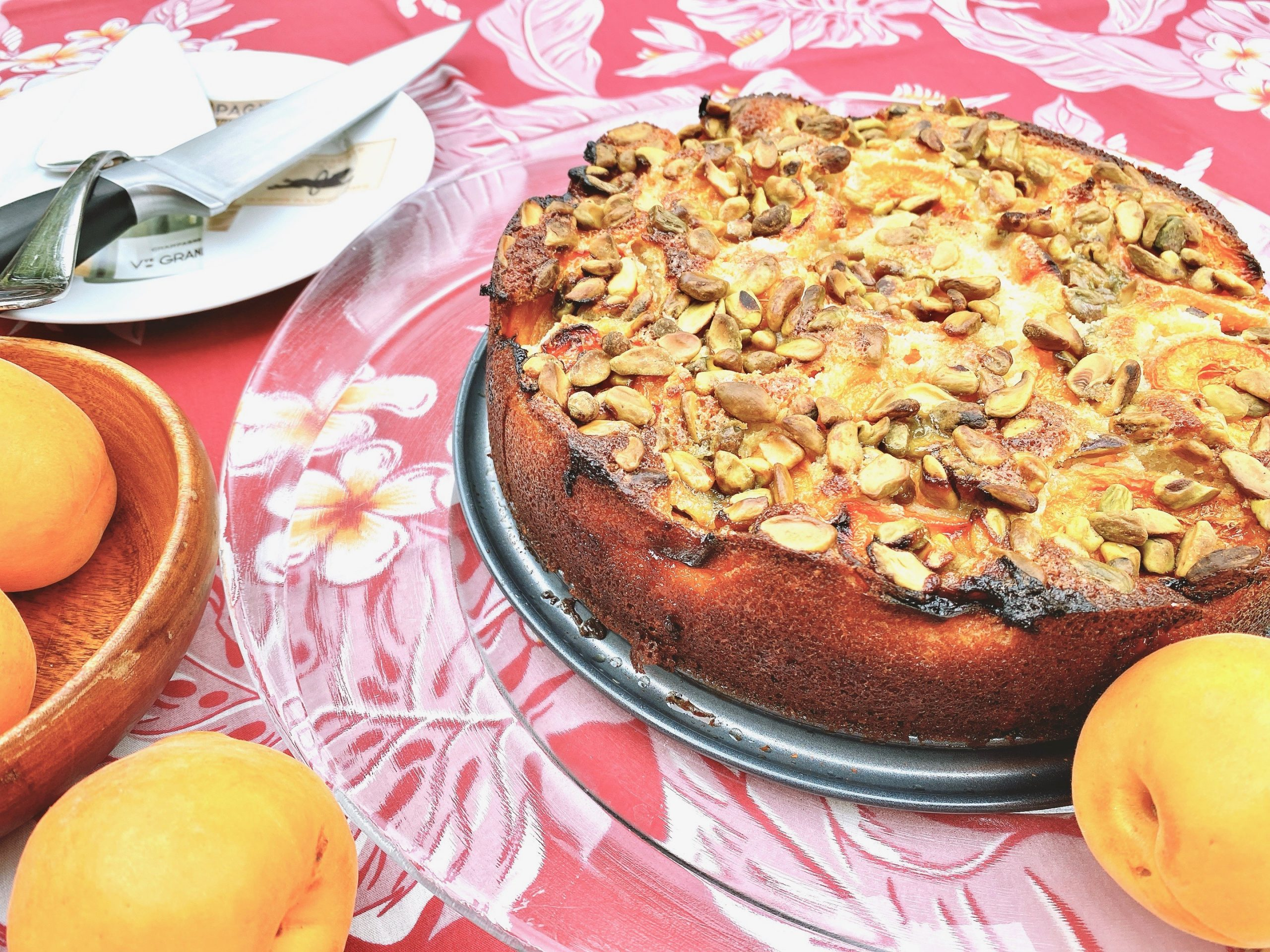 Whole Apricot Pistachio Cake on plate with fresh apricots and a Hawaiian themed tablecloth
