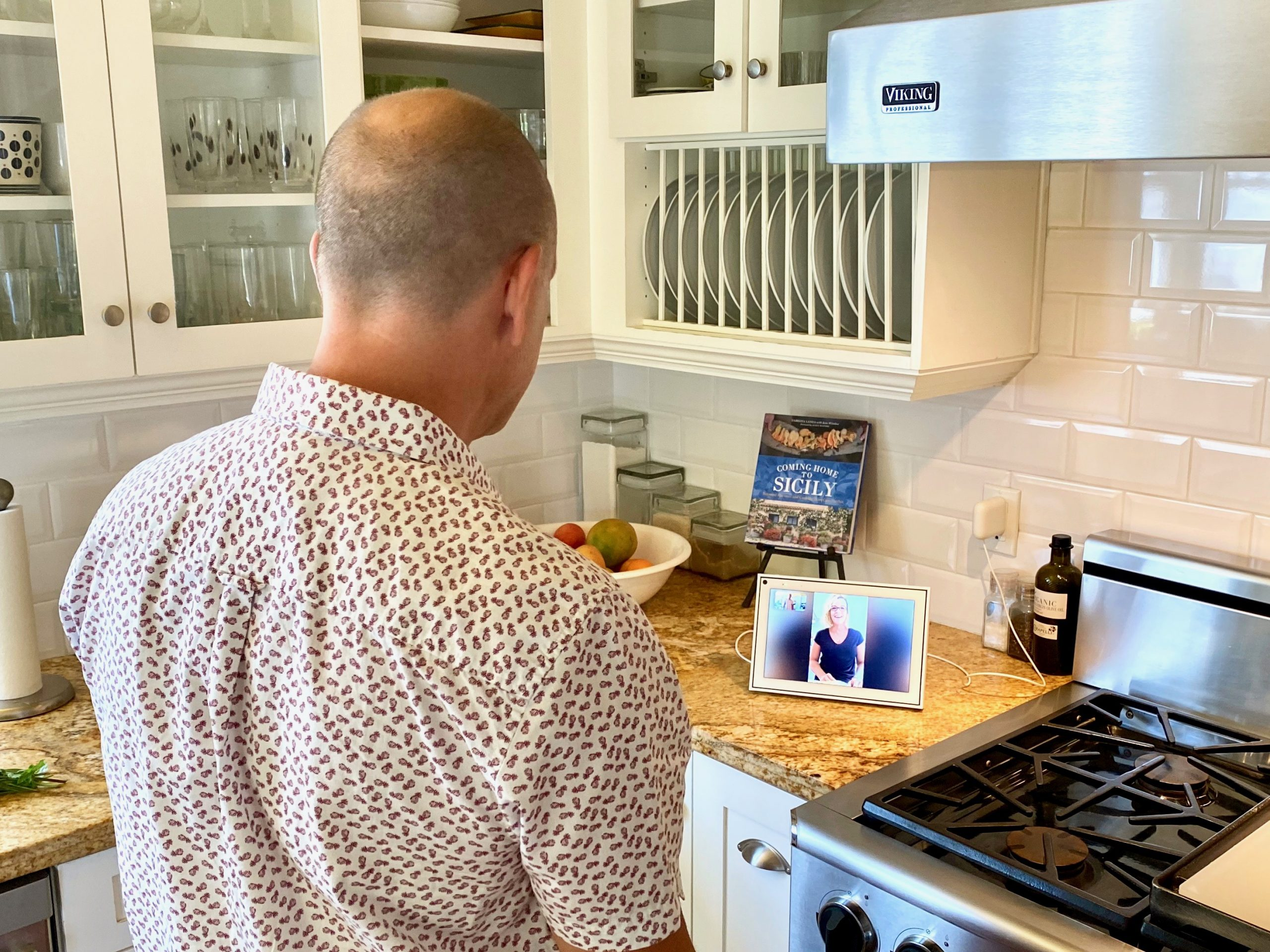 man uses Portal by Facebook in kitchen while videochatting with female friend