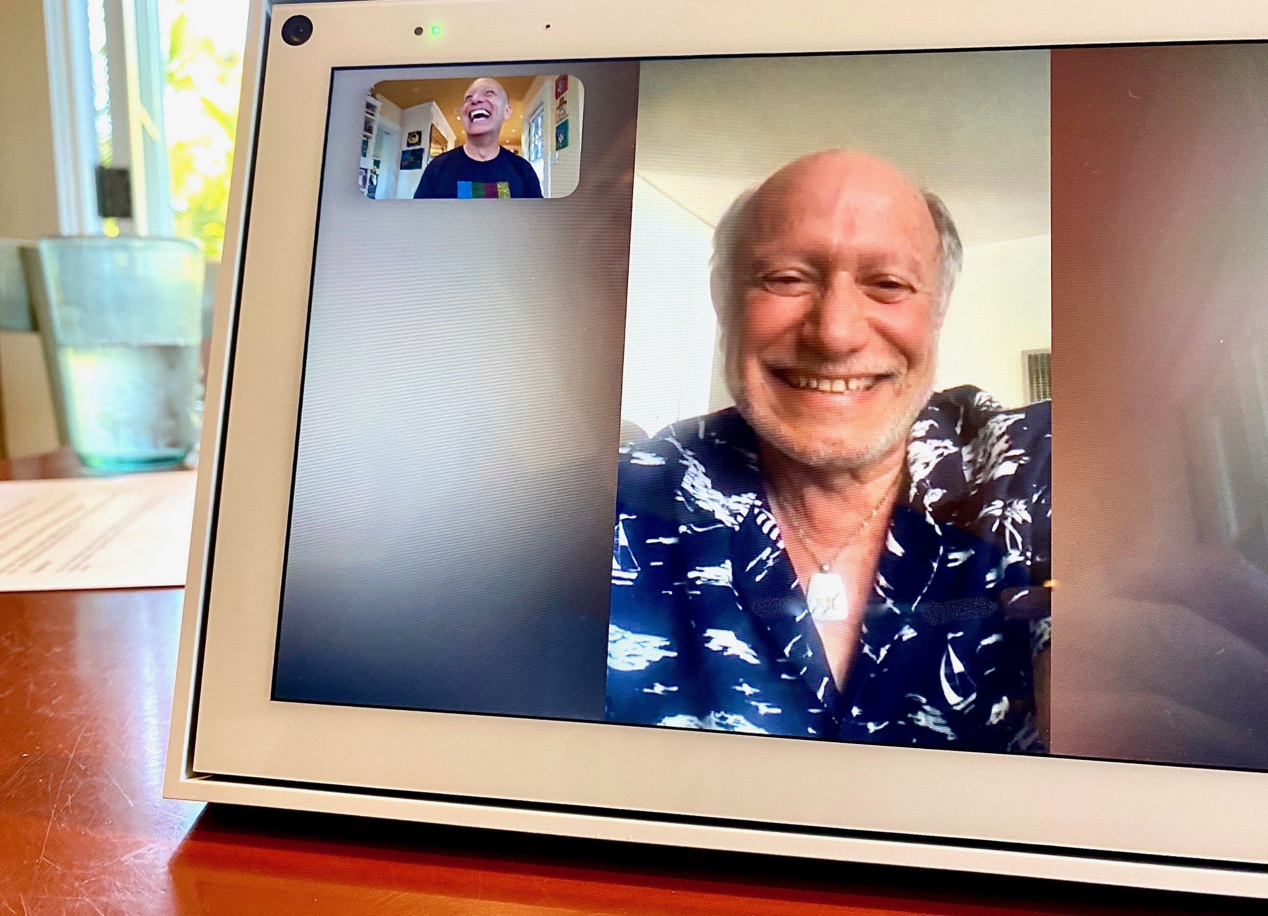 Two men laugh during video chat on Portal by Facebook.