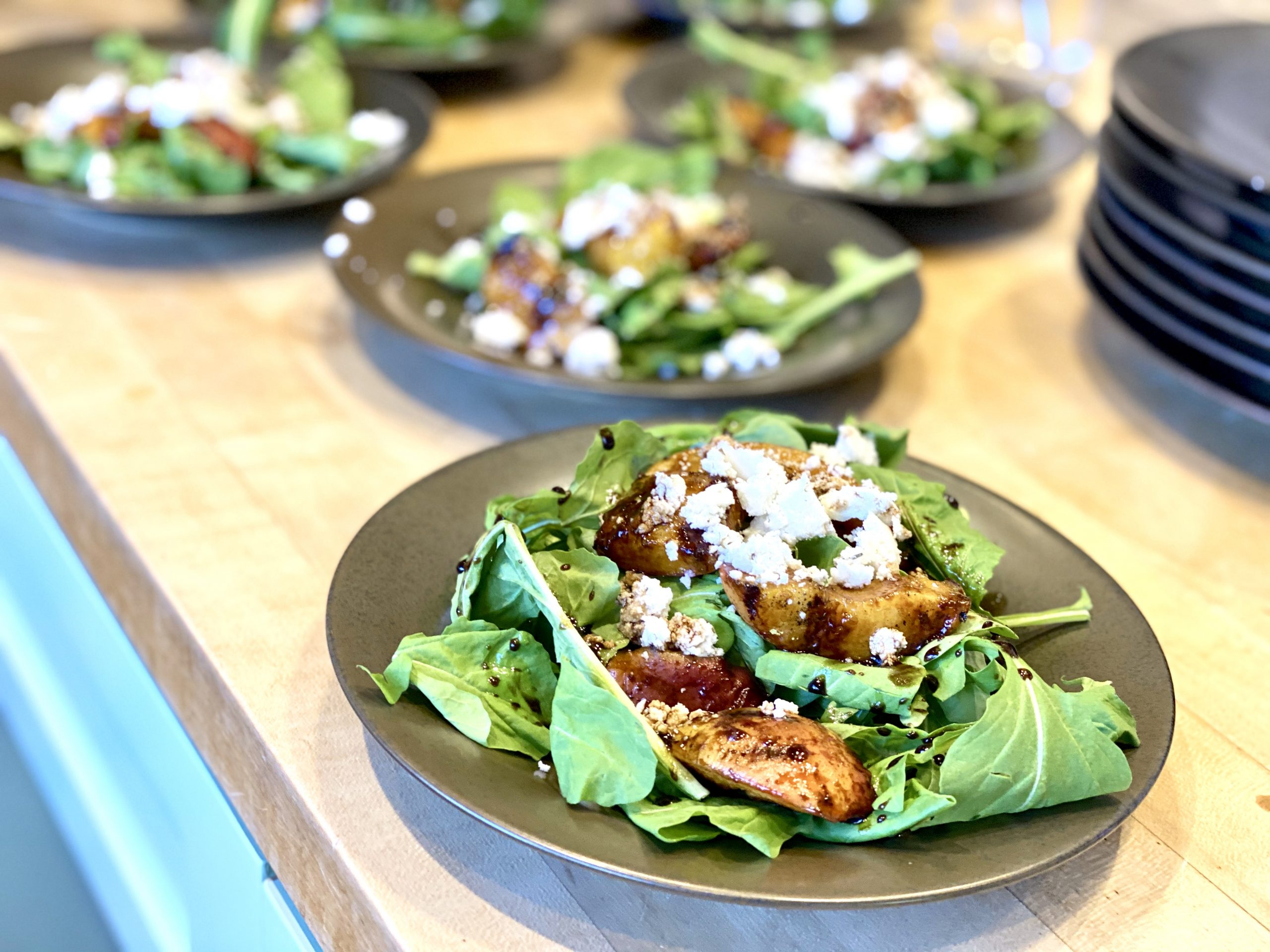 Homemade goat cheese topping a grilled peach salad with arugula and balsamic vinaigrette.