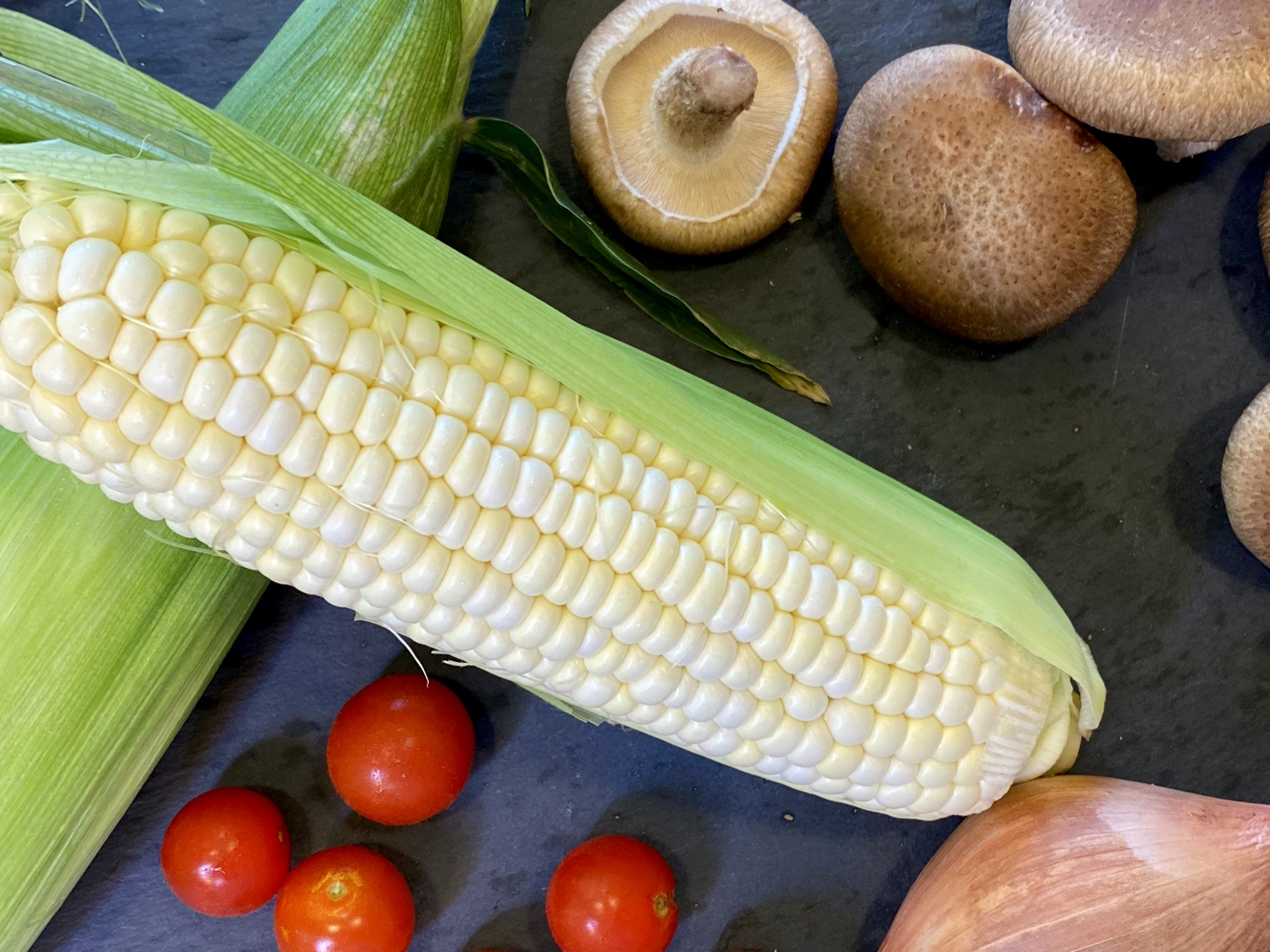 Fresh corn cob, mushrooms and cherry tomatoes ready to make Summer Pasta