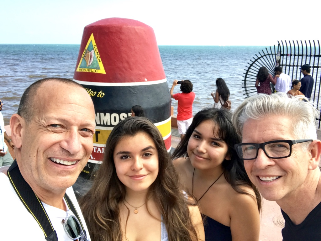 Family poses with southernmost tip of the US in Key West, Florida