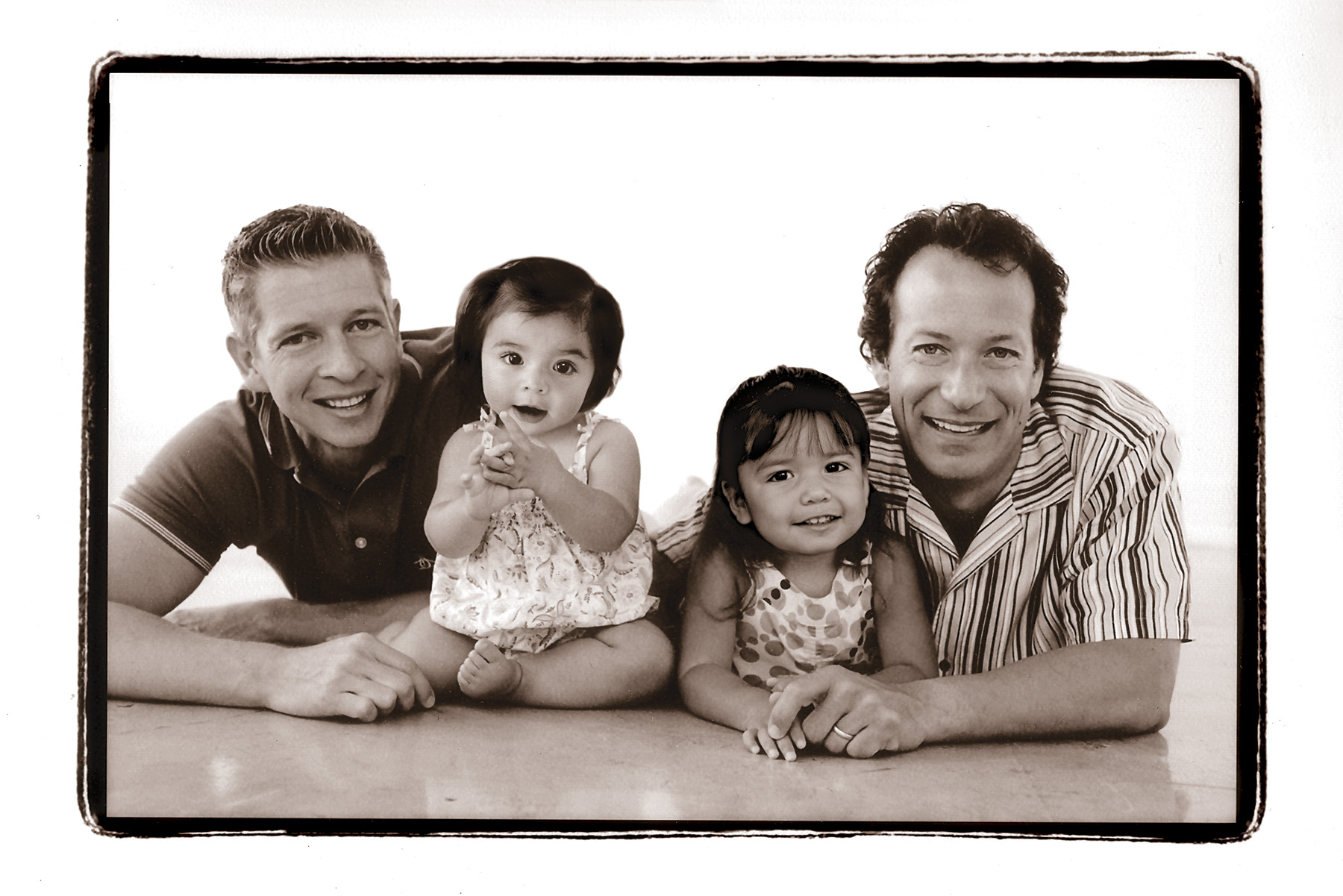 2 dads and their 2 young daughters in black and white studio shot, San Diego, CA