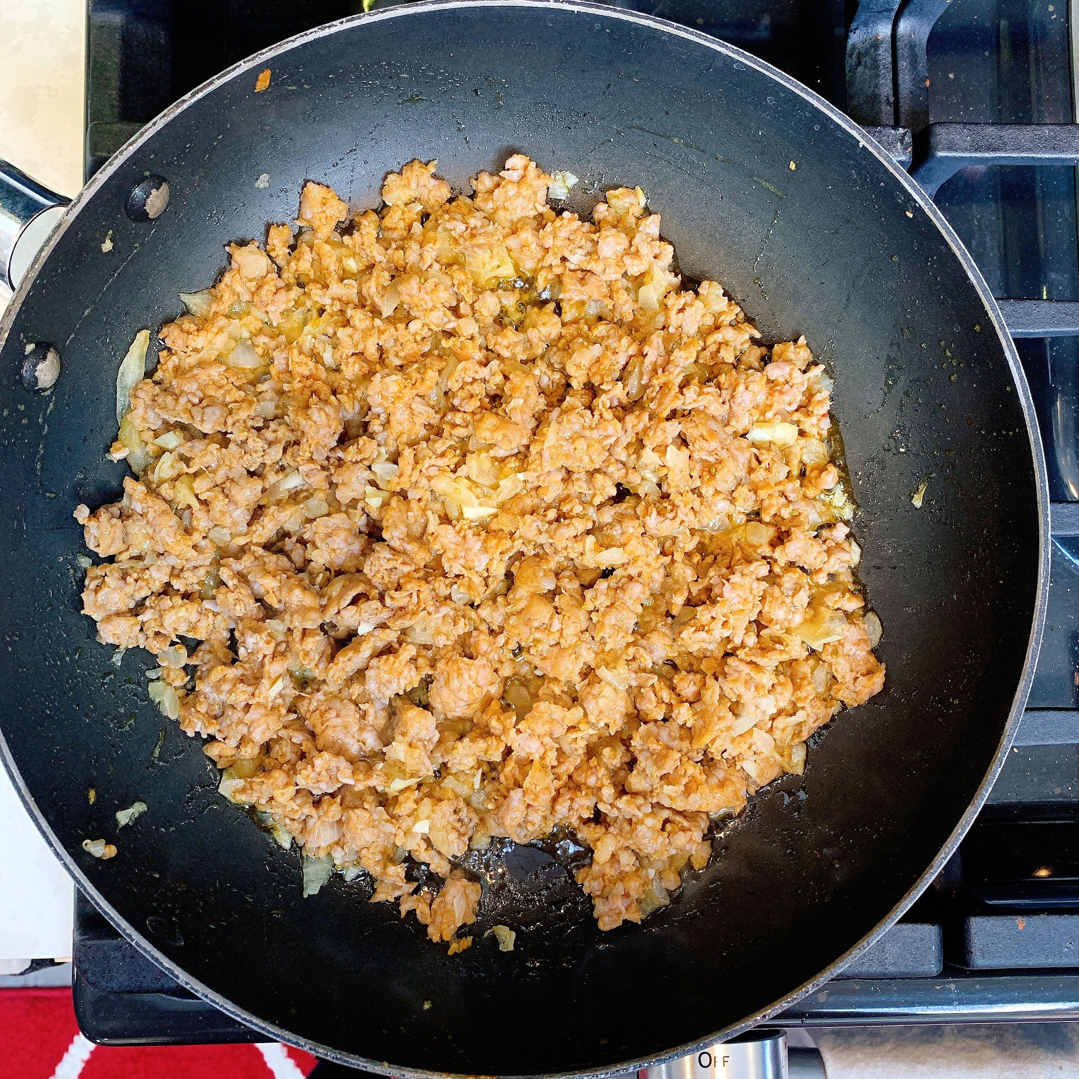 Italian sausage crumbles browning in a frying pan