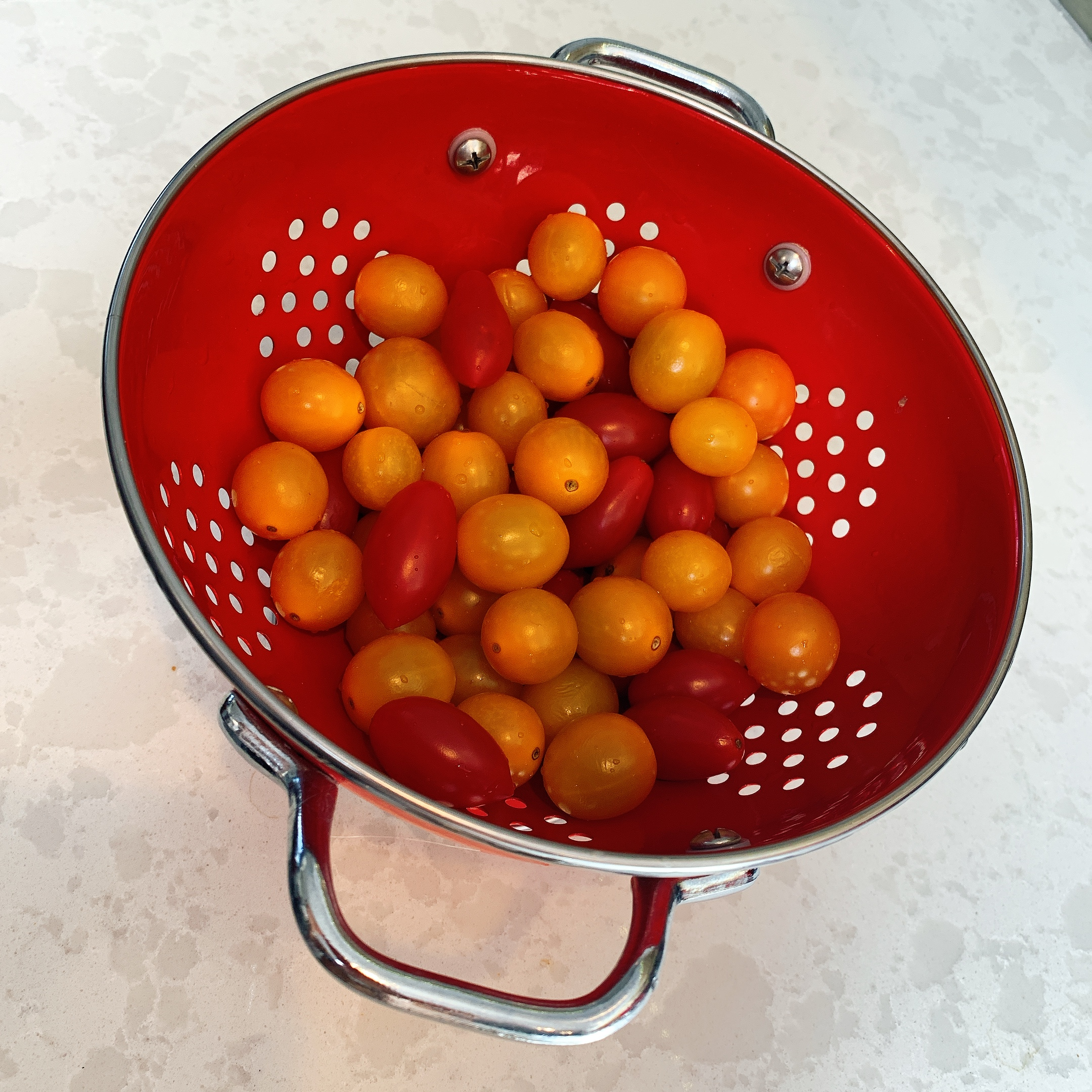 red colander filled with yellow and red cherry tomatoes