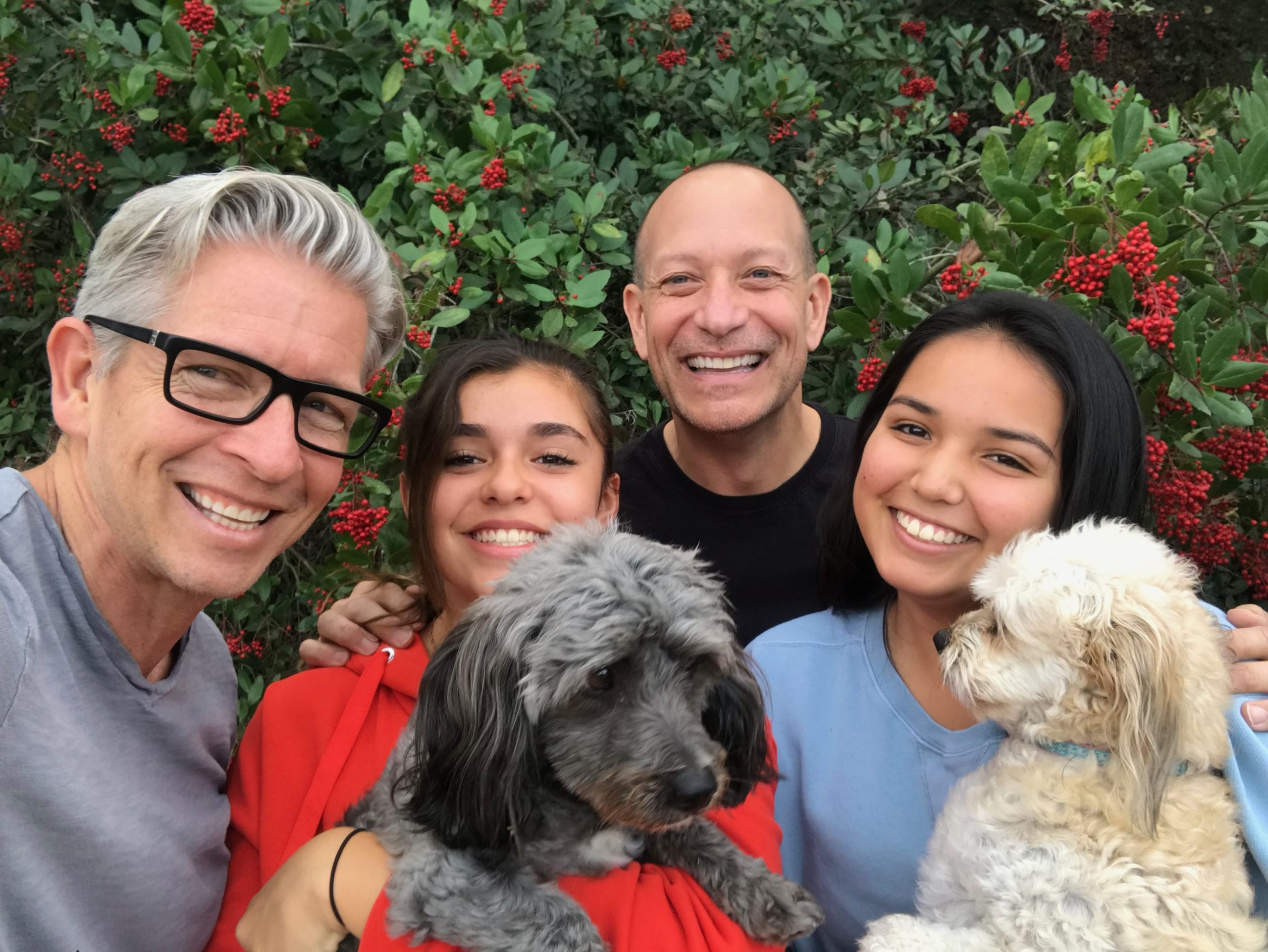 family with two dads and two teen daughters hold two dogs while smiling for camera in San Diego, CA