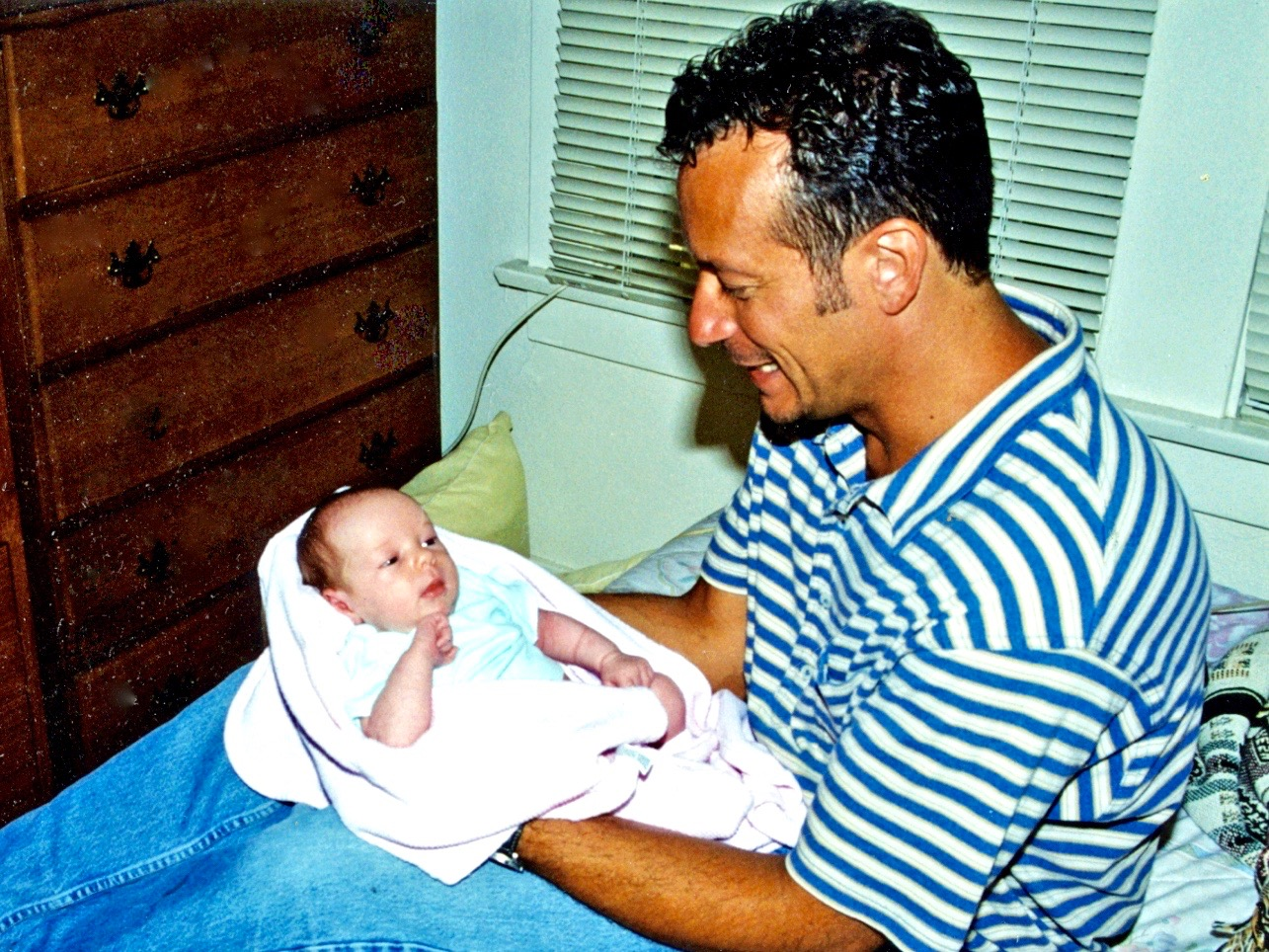 Man in the 1990s holding baby girl