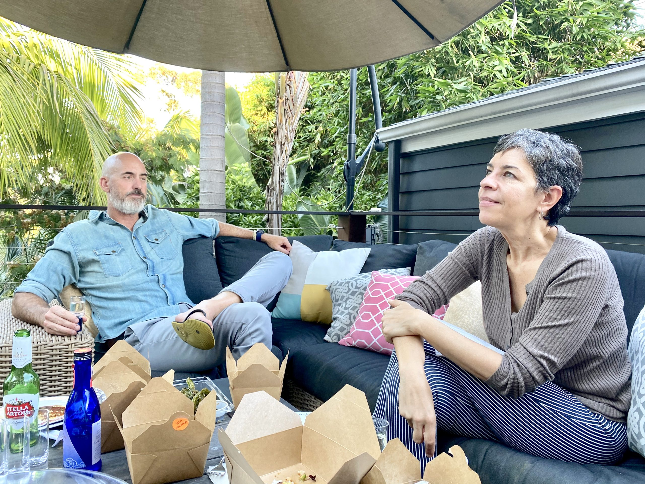 man and women enjoy picnic outside on deck with sake from Tippsy Sake