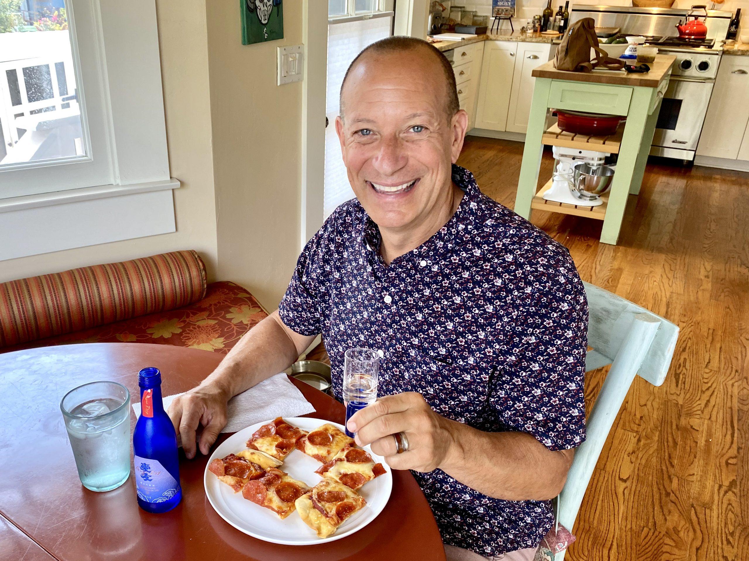 Man enjoying sake with pepperoni pizza